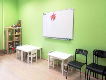В помещении есть доска для рисования, столы и стулья для малышей