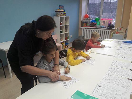 Преподаватель показывает правильное положение руки при письме